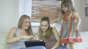 Young women and pretty little girl with tablet computer. Family with tablet at sofa. Woman and baby with tablet computer. Mother and daughter at home on sofa stock video