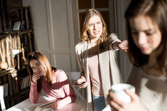 Young women quarreling. Angry young women holding smartphone and quarreling with brunette girl Stock Images