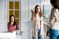 Young women quarreling. Angry young women holding smartphone and quarreling with brunette girl Stock Image