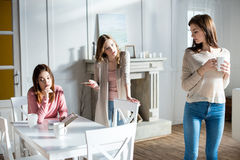 Young women quarreling. Three young women quarreling while drinking coffee at home Royalty Free Stock Image