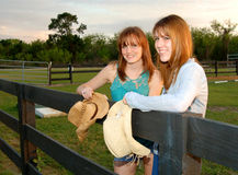 Young women at ranch. Two smiling young women in jeans, boots and cowboy hats outdoors on a fence at a ranch stock photography