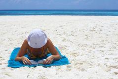 Young women is reading the book on the beach. Young women is reading the book on the coral beach, Maldives royalty free stock images