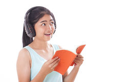 Young women reading book and listening music Stock Images