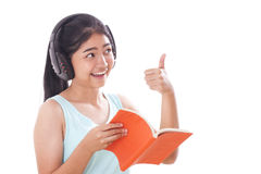 Young women reading book and listening music Royalty Free Stock Photo
