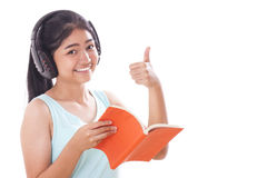 Young women reading book and listening music. Young woman reading book and listening music and showing thumb up Stock Photos