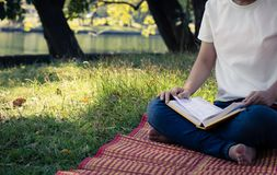 Young women reading book in park, concept in knowledge and educa. Tion Royalty Free Stock Photos