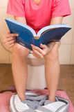Young women reading a book while sitting in the toilet. Royalty Free Stock Photo