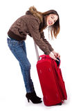 Young women ready for winter travel. Checking her suitcase indoor studio Stock Image