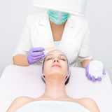 Young woman receiving facial treatment stock images