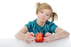 Young women with a red apple on the table. Royalty Free Stock Photos