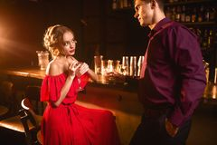 Woman in dress flirts with man behind bar counter Stock Photos