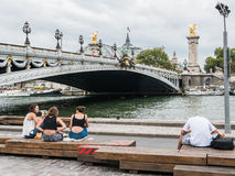 Young women relax on the Berges de Seine near the Grand Palais, Paris Royalty Free Stock Image
