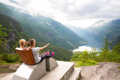 Young women relax on Geiranger fjord. Happy friends enjoy beautiful lake and good weather in Norway. Stock Photography