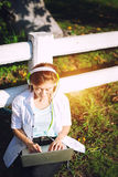 Young women relaxation listening music with notebook sitting on the grass. Royalty Free Stock Images