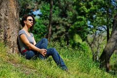 Young women relaxes in the green. Curly haired young women relaxes in the green park, sitting under a tree Stock Photo