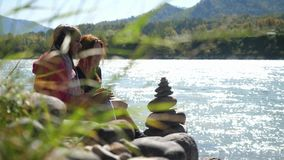 Young women relaxing on nature by pebble stack next to the mountain river in sunny day. Royalty Free Stock Photo