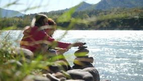Young women relaxing on nature putting pebble stack next to the mountain river in sunny day. Royalty Free Stock Photo