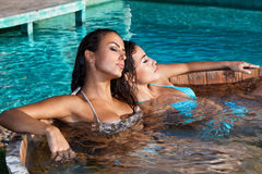 Women in jacuzzi. Young women relaxing in outdoor jacuzzi by the pool summer day stock photos