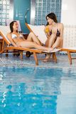 Young women by the pool Royalty Free Stock Images
