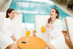 Young women relaxing by pool Royalty Free Stock Image