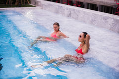 Young women relaxing by the pool royalty free stock photography