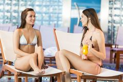 Young women relaxing by the pool Royalty Free Stock Image