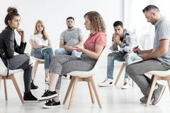 Young woman resolving problem with rebellious friend during group therapy with counselor. Young women resolving problem with rebellious friend during group royalty free stock photos