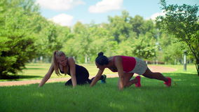 Young women rest after push ups exercise outdoor. Fitness women doing push up exercise. Two women doing pushups exercise in park. Women pushing on green grass stock video