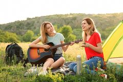 Young women resting with hot drink and guitar. Near camping tent in wilderness stock photos