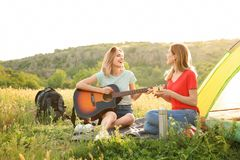 Young women resting with hot drink and guitar. Near camping tent in wilderness royalty free stock image