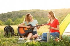 Young women resting with hot drink and guitar. Near camping tent in wilderness royalty free stock photography