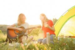 Young women resting with hot drink and guitar. Near camping tent in wilderness royalty free stock photos