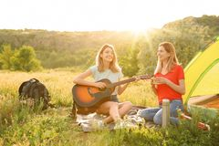 Young women resting with hot drink. And guitar near camping tent in wilderness stock image