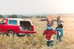 Young women riding on boyfriends shoulders in field during. Car trip stock photography