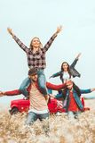 young women riding on boyfriends shoulders and raising hands stock photo