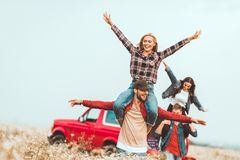 Young women riding on boyfriends shoulders and raising hands in field during. Car trip royalty free stock image