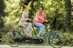 Young women riding on the tandem bicycle Royalty Free Stock Photo