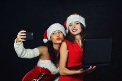 Young women in Santa hats with laptop and phone royalty free stock image