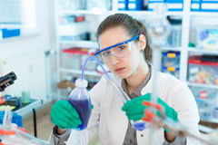 Young women science professional pipetting solution into the glass test Stock Photos