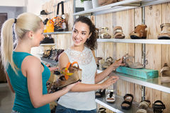 Young women selecting shoes. Ttwo glad beautiful young women selecting shoes and chatting among shelves Royalty Free Stock Photography