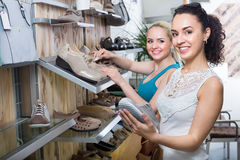 Young women selecting shoes. Ttwo glad young women selecting a shoes and chatting among a shelves. Focus on right person Stock Images