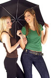 Young women sharing umbrella Stock Photography