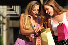 Young women shopping. Two young women sharing their new purchases with each other Stock Photography