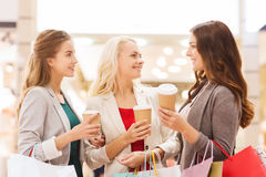 Young women with shopping bags and coffee in mall. Sale, consumerism and people concept - happy young women with shopping bags and coffee paper cup in mall Stock Photography