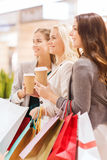 Young women with shopping bags and coffee in mall. Sale, consumerism and people concept - happy young women with shopping bags and coffee paper cup in mall Royalty Free Stock Image