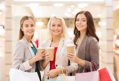 Young women with shopping bags and coffee in mall. Sale, consumerism and people concept - happy young women with shopping bags and coffee paper cup in mall Royalty Free Stock Photography