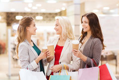 Young women with shopping bags and coffee in mall. Sale, consumerism and people concept - happy young women with shopping bags and coffee paper cup in mall Stock Photo