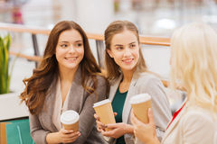 Young women with shopping bags and coffee in mall. Sale, consumerism and people concept - happy young women with shopping bags and coffee paper cups in mall Royalty Free Stock Photos