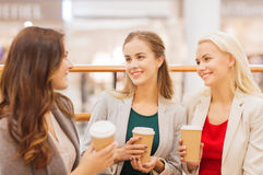 Young women with shopping bags and coffee in mall. Sale, consumerism and people concept - happy young women with shopping bags and coffee paper cups in mall Stock Photo