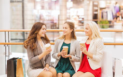 Young women with shopping bags and coffee in mall. Sale, consumerism and people concept - happy young women with shopping bags and coffee paper cups in mall Royalty Free Stock Image